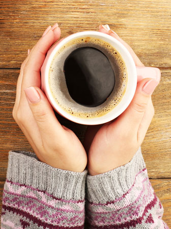 female hands holding a cup of coffee from below